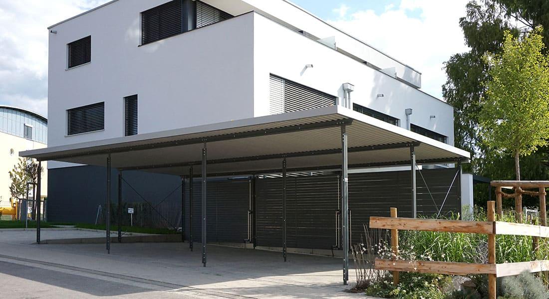 Reihen-Carport mit 3 Stellplätzen, Dach mit extensiver Begrünung und Wandelemente aus Trapezprofil, Lärche vorvergraut
